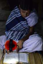 Hasina Khatun using her new solar lamp
