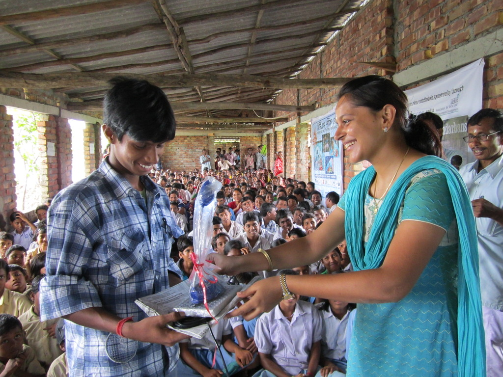 A student receiving a lamp from Ekta of ONergy