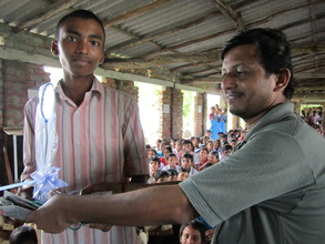 Student receiving a lamp from Sushanta of BTS