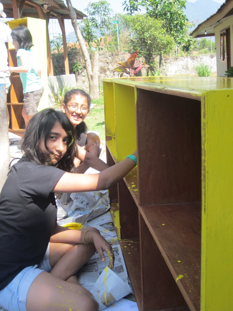 JIS students helping to repaint the shelves