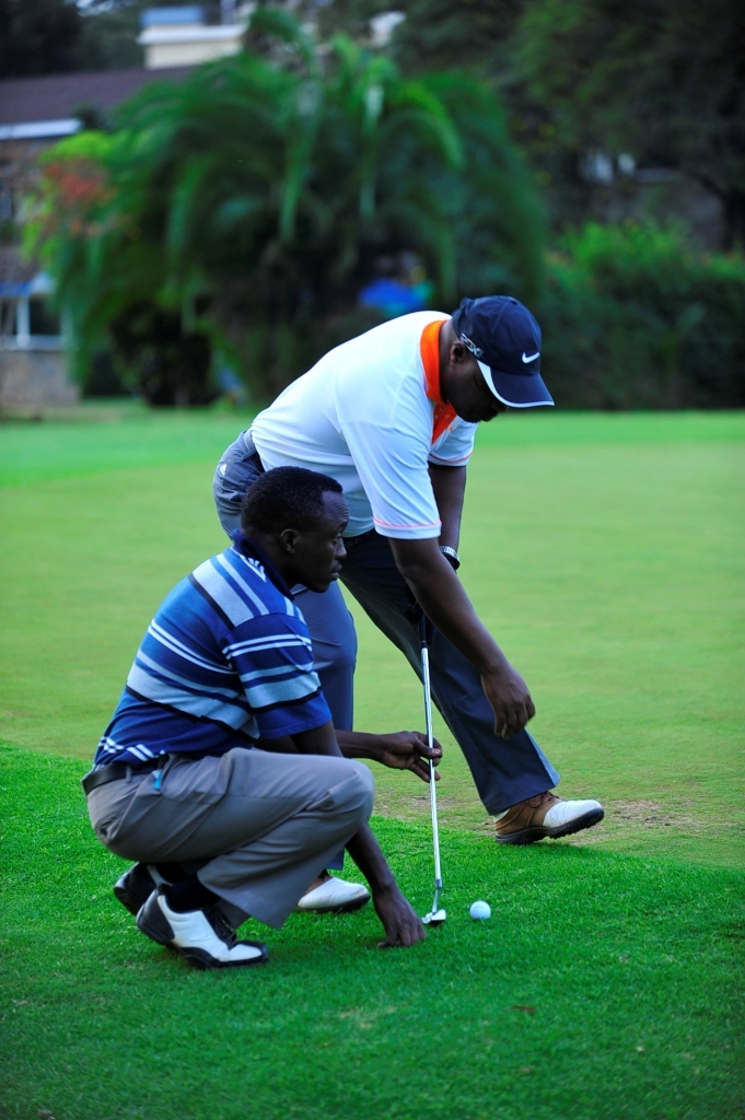 A blind golf player with his guide on the green.
