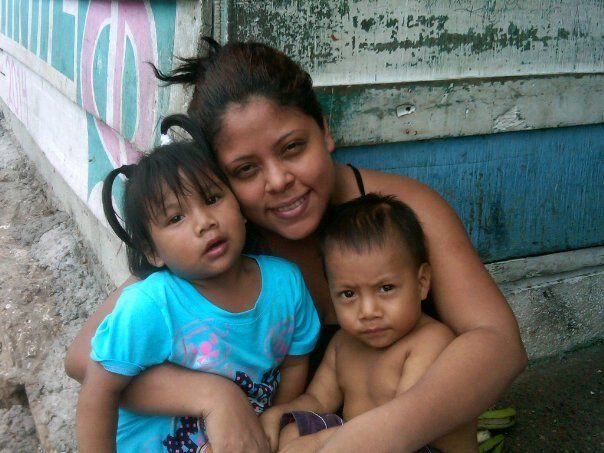 Carmela outside her home with her children