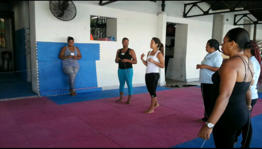 Standing by herself during yoga class (far left)