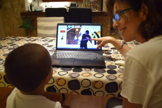 Hearing mother with deaf child enjoying videobooks