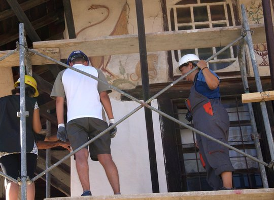 Trainees documenting visible painting under eaves