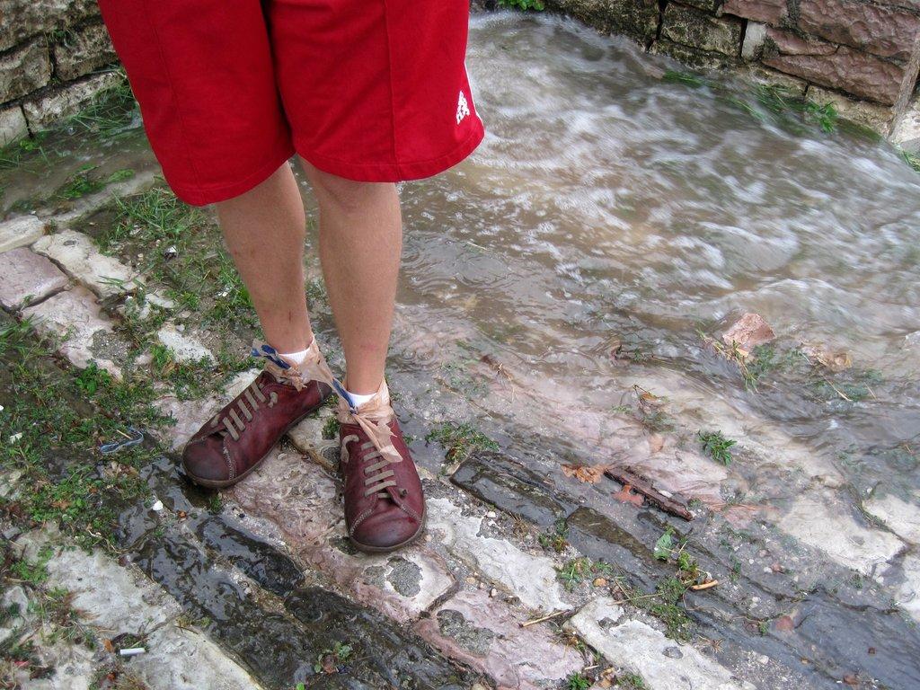 Rain runs down stone streets during deluge