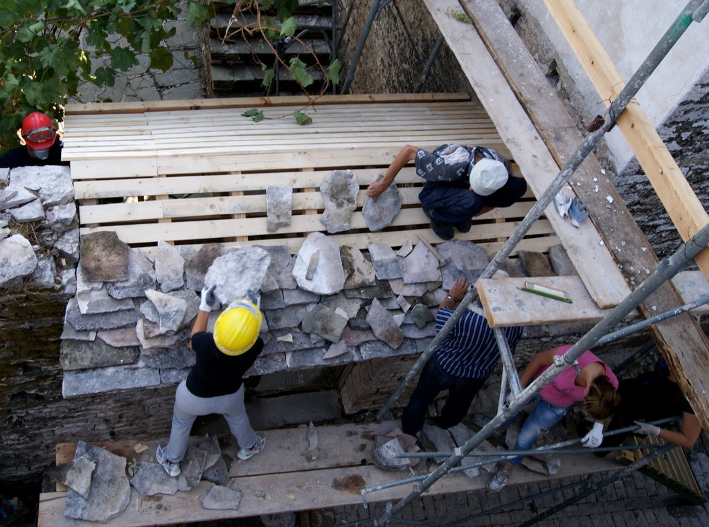 Trainees lay new stone roof over entry gate