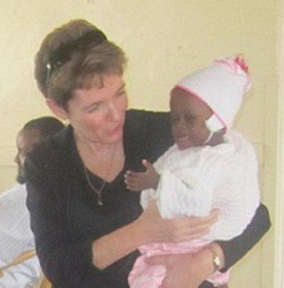 Little Jolie held by visiting team member