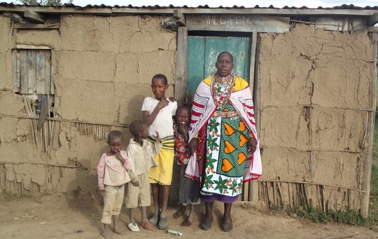 Pelete Parkire and family outside dung house
