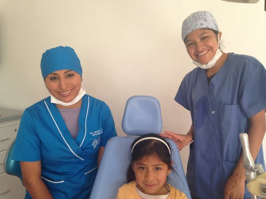Dr. Nayda A. in blue dental cap & Hygienist Adela