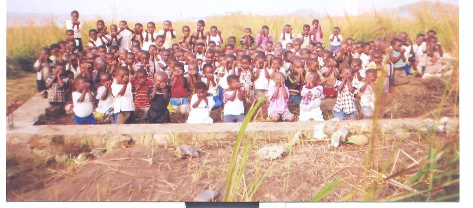 Pupils of Glenn Paige Nonkilling School (kazimia) are praying to God at the site of their school under constuction for donors and to finish construction.