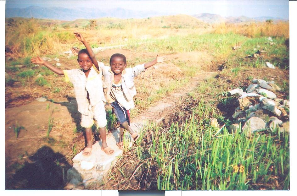 Two pupils pose merrily on the foundation of their school building.