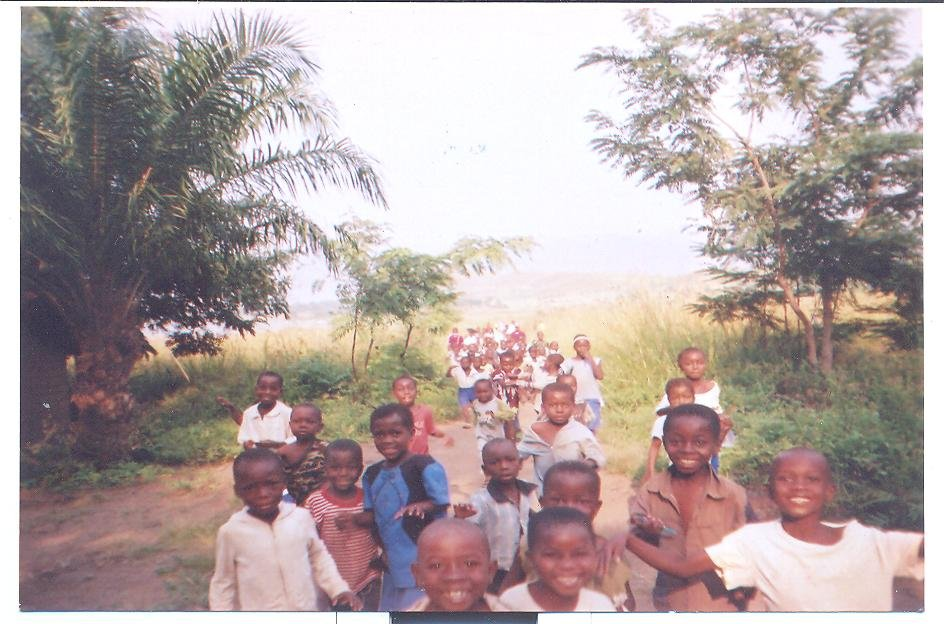 Pupils are returning from  the site of their school where they were praying. They are optimistic and cheerful.