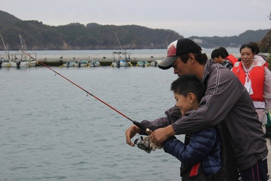Children being taught by fishermen.