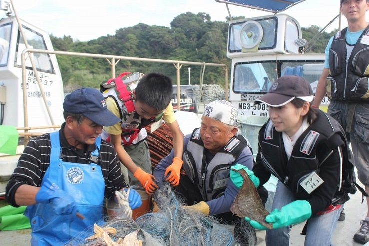 Volunteers and locals catch fish together.