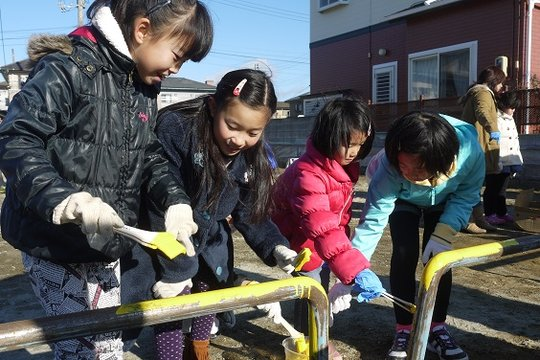 Children painting on playground equipment