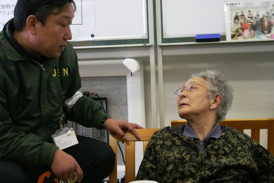 JEN staff visits with a woman in temporary housing