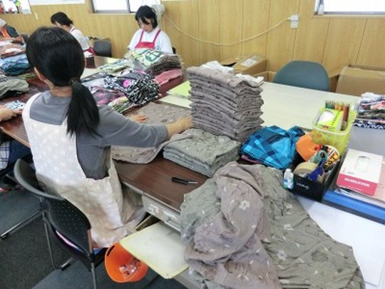 The facility user folds and bags the clothes