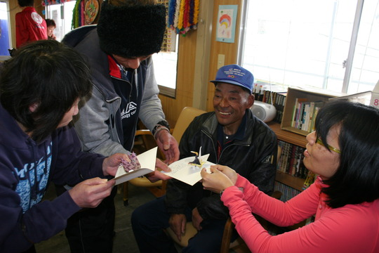 Mari gives cards to Mr. Abe and other residents
