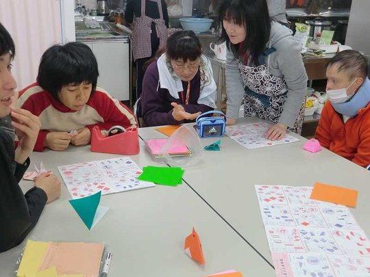 People at Nozomi workshop practicing paper folding