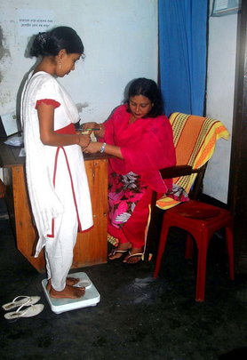 A paramedic taking weight of a patient