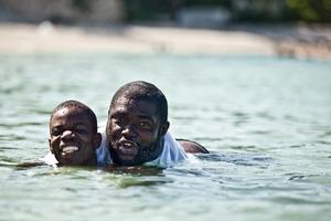 Samuel taking his first swim on Gary's back