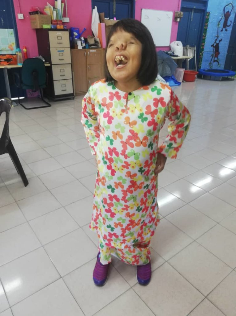 Siti loves to smile and stay happy
