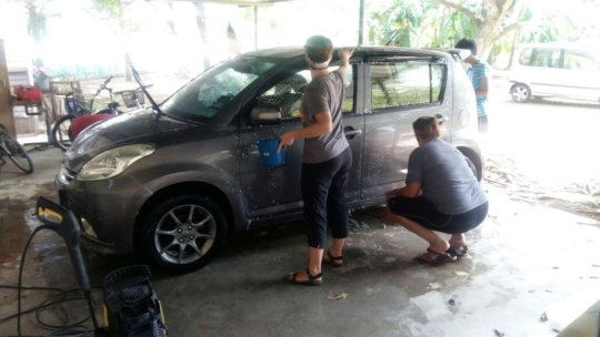 Volunteers helping to wash a car