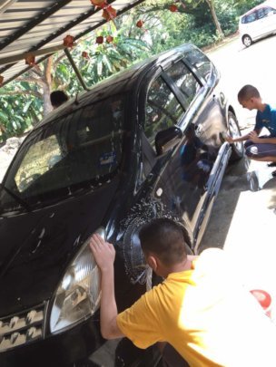 Trainees cleaning a car for CNY car wash event