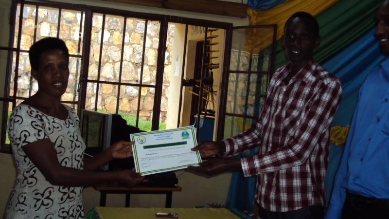 The women receiving a certificate from her teacher