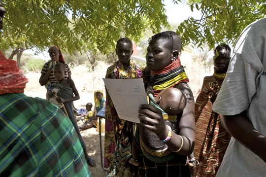 A Turkana mother clutches her health report card