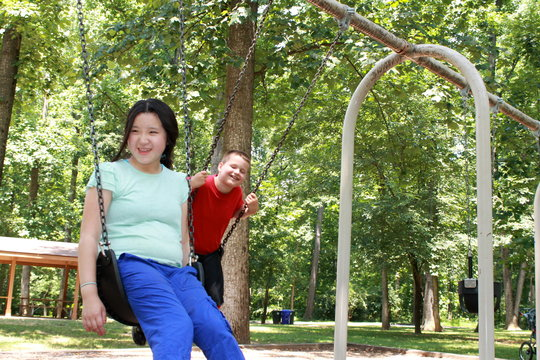 Swinging with friends in the public park