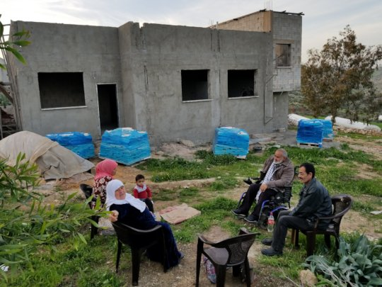 A family chats outside their near-finished home