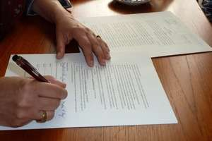My hand on the Agreement as I sign