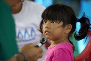 A little girl listens intently to Dr. Saul Camacho