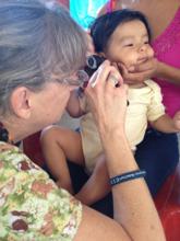 CERI medical volunteer treats baby