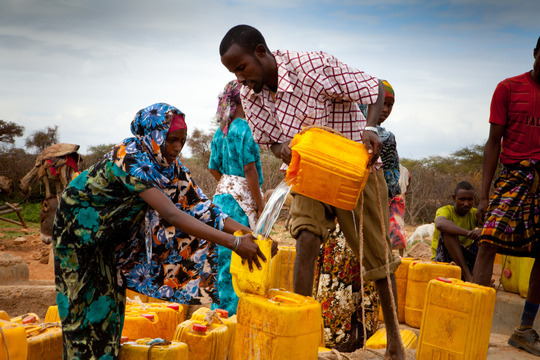 People help one another retrieve water