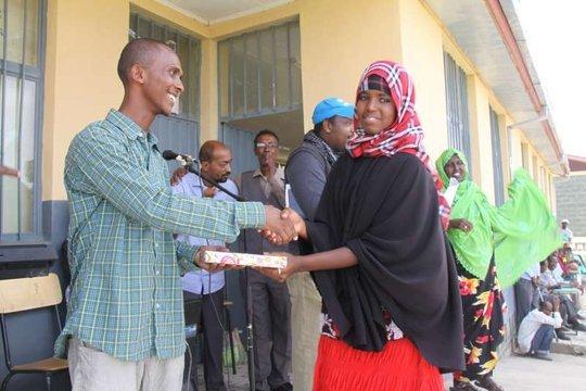 Somali refugee gets an English-Somali dictionary
