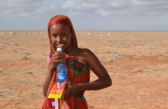 Girl receives food and water from Mercy Corps