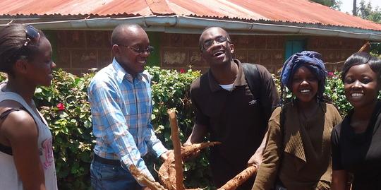Michael and the PATHWAYS scholars holding cassava