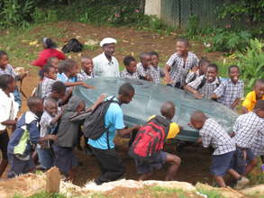 Children helping to bring tank lid to their school