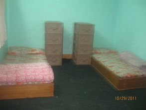 Two beds and dressers in one room