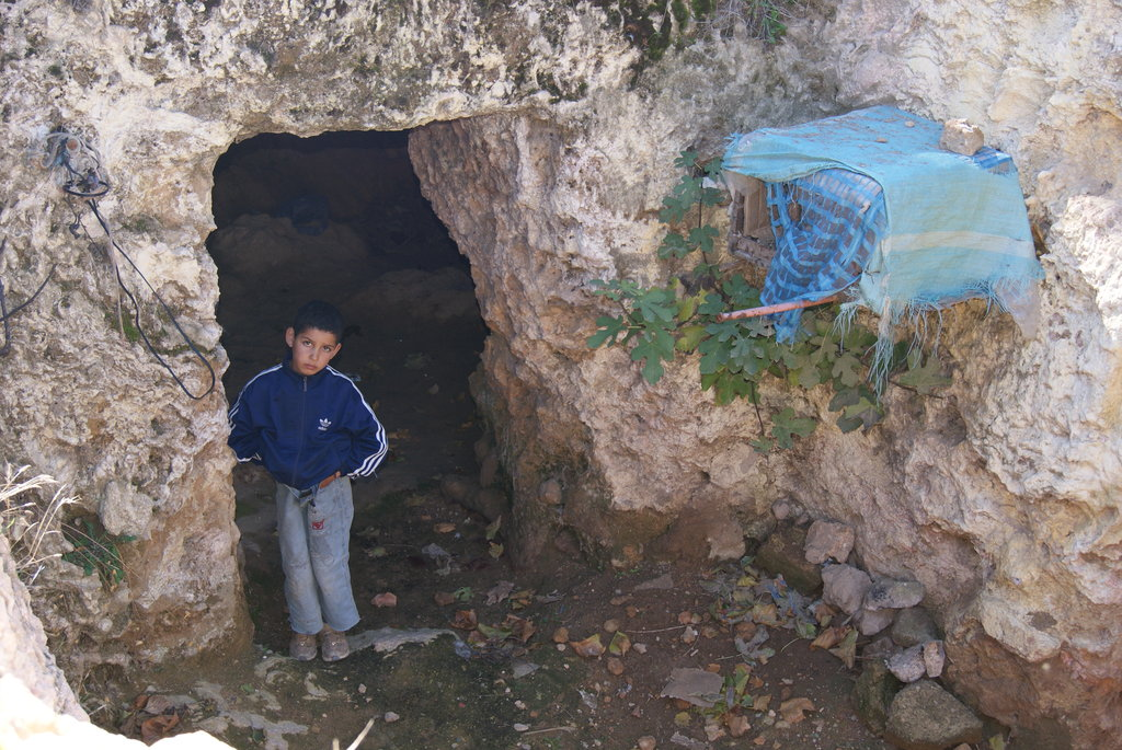 ?Child living in natural caves in Morocco?.  These underprivileged children often live alone with their mother under very difficult conditions in the mountains, especially during winter.  They rarely go to school and they have little hope for their future.