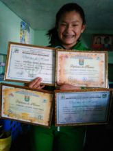 Andrea holding 4 of her valedictorian diplomas.