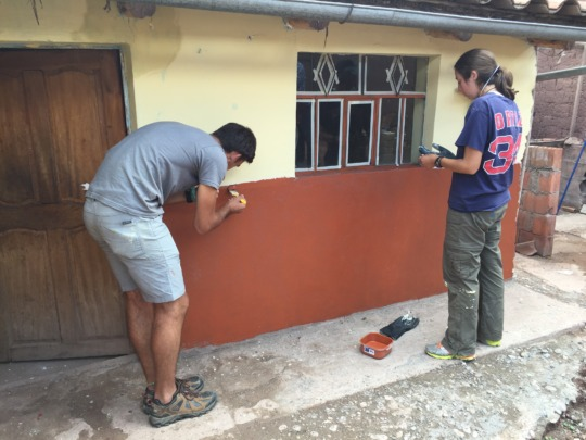 An ARCC student volunteer paints Epi's house