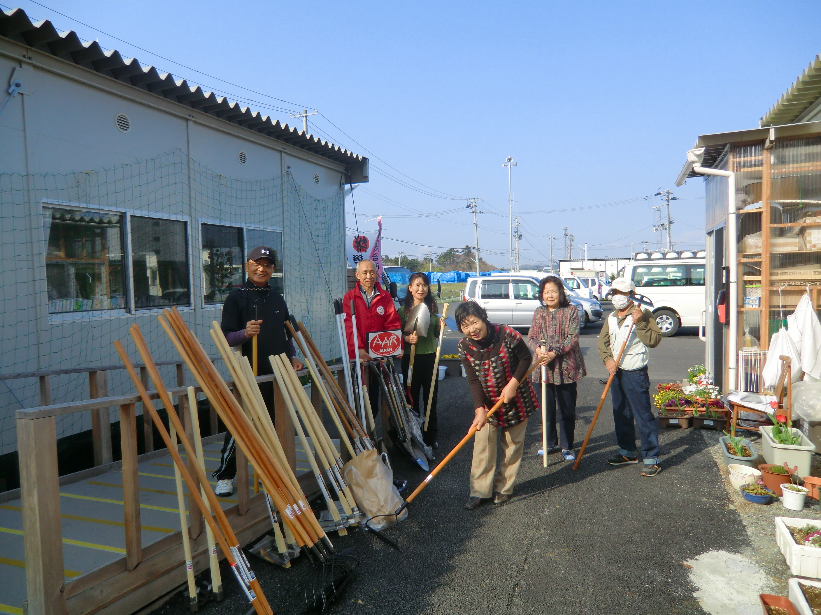 Distribution of farming tools to residents of temporary housing complexes in the disaster-affected area of the Tohoku region, in the effort to revitalize the community through agricultural activities.