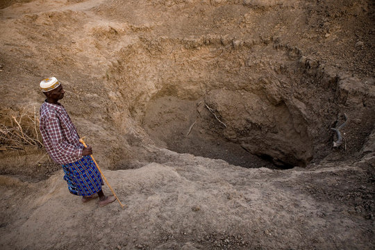 Abdikadir looks down at a dry earth well