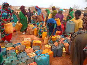Refugees wait to clean jerry cans.