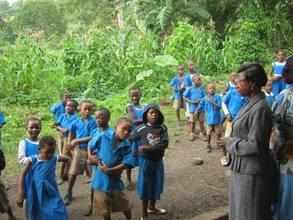 Pupils singing to welcome SDI staff