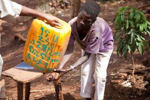A boy washes his hands with clean water